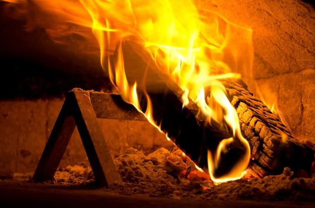 Primer plano de fuego dentro de un horno de pizza en italia