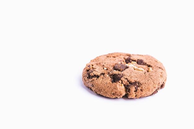 Primer plano de una galleta con chispas de chocolate aislado sobre un fondo blanco.