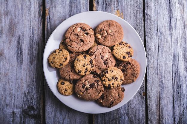 Primer plano de galletas con chispas de chocolate en un plato blanco sobre una superficie de madera