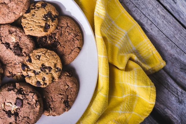 Primer plano de galletas de chispas de chocolate recién horneadas en una placa blanca sobre un textil amarillo