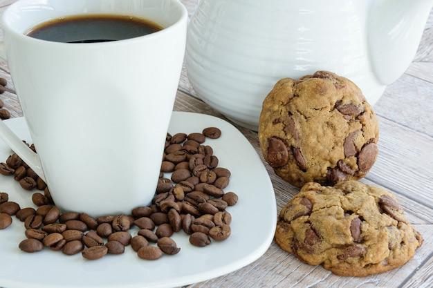 Primer plano de galletas de gotas de chocolate apoyadas en la tetera. junto a la taza y los granos de café.