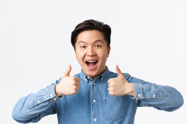 Primer plano de ganador exitoso, feliz hombre asiático con aparatos dentales sonriendo ampliamente y mostrando el pulgar hacia arriba en señal de aprobación, alabando el gran trabajo, diciendo bien hecho, de pie fondo blanco complacido
