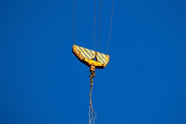 Primer plano del gancho de la grúa. concepto de operación y elevación de carga, fondo de cielo azul