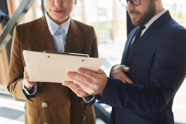 Primer plano de gente de negocios con portapapeles que firman el contrato en la oficina