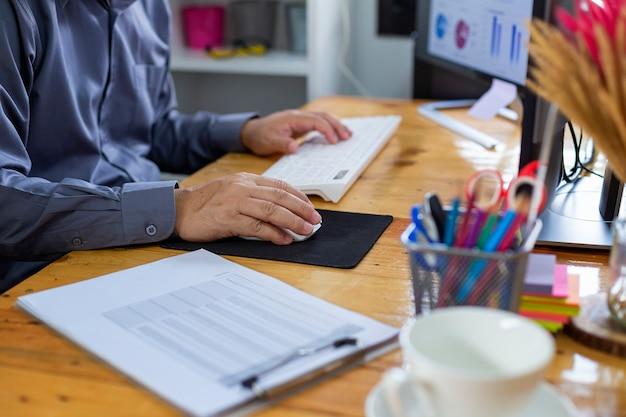 Primer plano de gente de negocios que debería estar observando datos de hojas y computadoras para una planificación comercial cuidadosa.