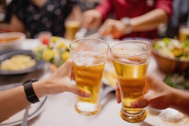 Primer plano de gente vitoreando cerveza en una fiesta. grupo de asiáticos que tienen una fiesta de año nuevo en casa.