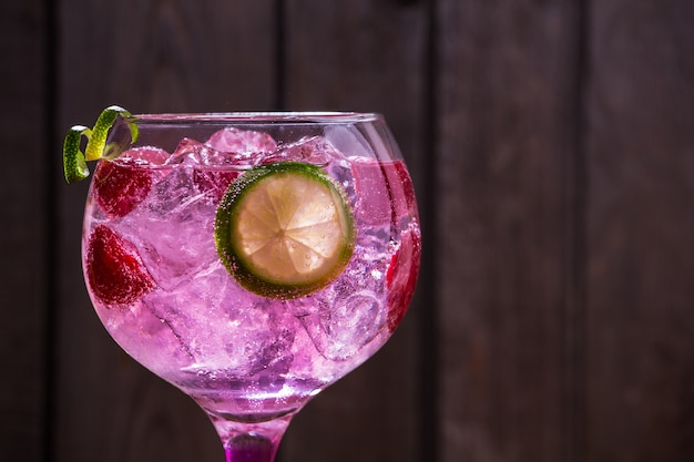 Primer plano de gin tonic rose con frambuesas y lima