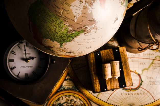 Primer plano del globo, reloj y mapa histórico
