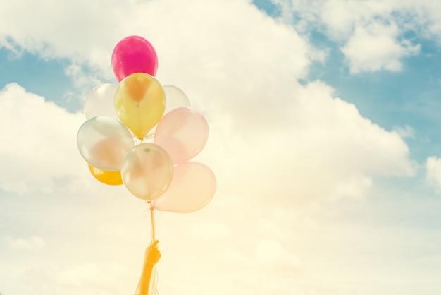 Primer plano de globos de colores con el cielo de fondo