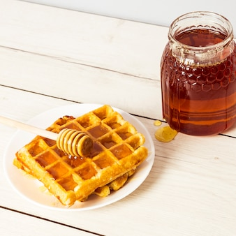 Primer plano de gofres deliciosos y miel en placa sobre superficie de madera