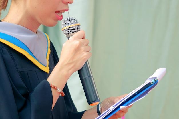 Primer plano graduados mano sostener micrófono maestro de ceremonia aniversario