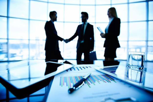 Primer plano de gráfico de barras con ejecutivos negociando de fondo