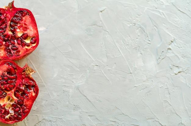 Primer plano de granadas maduras rojas - cortadas y en rodajas, maduras y sabrosas con espacio de copia, fondo de cemento gris