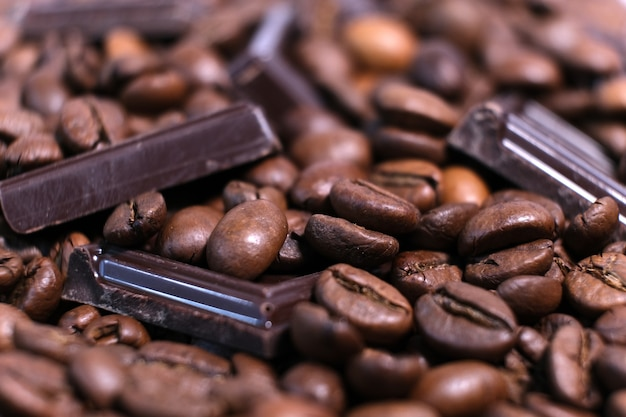 Primer plano de granos de café aromáticos tostados oscuros y fondo de chocolate