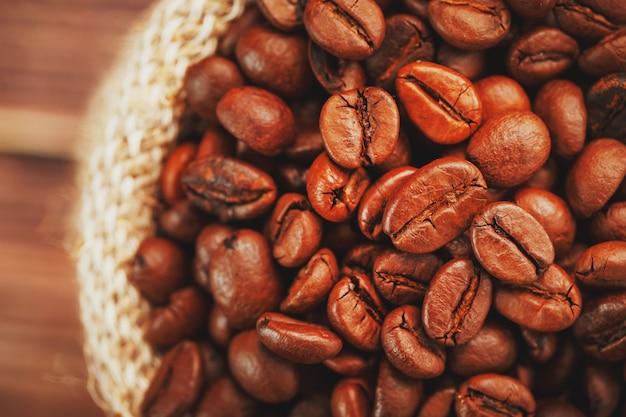 Primer plano de granos de café en bolsa de arpillera sobre superficie de madera contraste suave granos de café tostados aromáticos