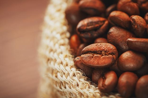 Primer plano de granos de café en bolsa de arpillera sobre superficie de madera