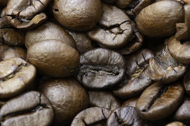 Primer plano de granos de café tostados bajo las luces con bordes borrosos