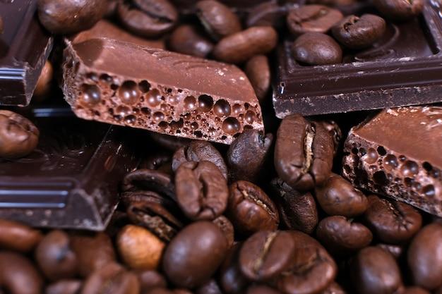 Primer plano de granos de café tostados oscuros y fondo de chocolate.