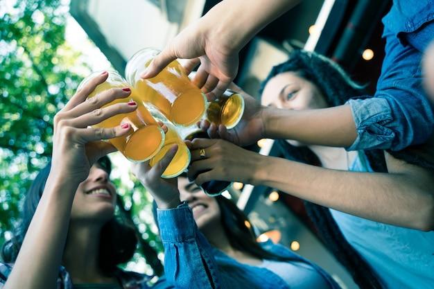 Primer plano de un grupo de amigos brindando con cerveza en un jardín de cerveza.