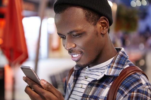 Primer plano de un guapo hipster barbudo joven de piel oscura que lleva una mochila sobre sus hombros leyendo mensajes en línea a través de las redes sociales