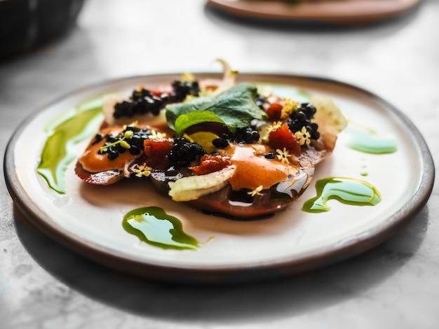 Primer plano de una guarnición con verduras y caviar en la parte superior con fondo borroso