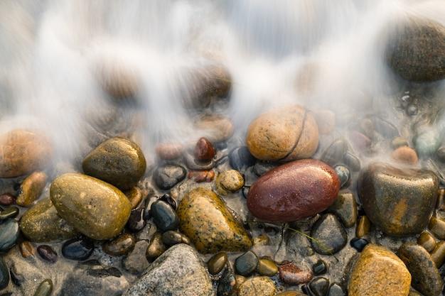 Primer plano de guijarros cubiertos con espuma de mar
