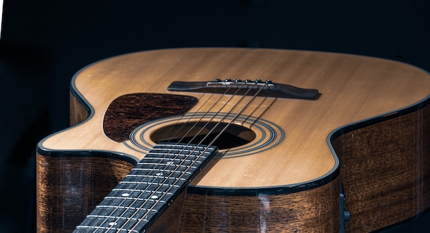 Primer plano de una guitarra acústica clásica sobre un fondo negro.