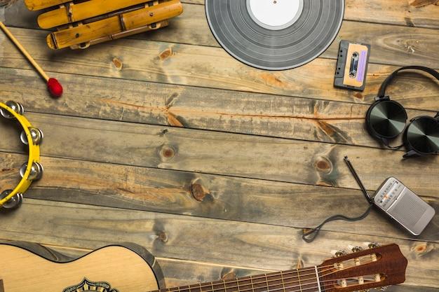 Primer plano de la guitarra; auricular; pandereta; xilófono; auriculares y radio en mesa de madera