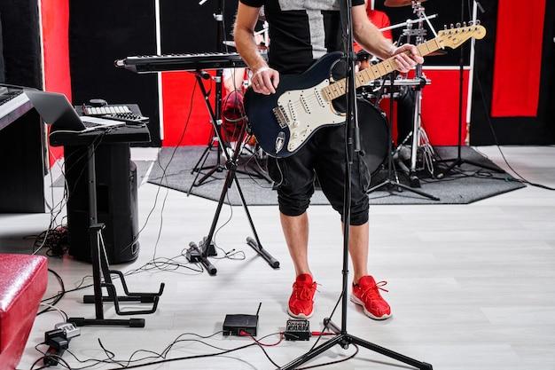 Primer plano del guitarrista de la banda musical tocando una guitarra eléctrica con el telón de fondo de la base de ensayo, sin rostro