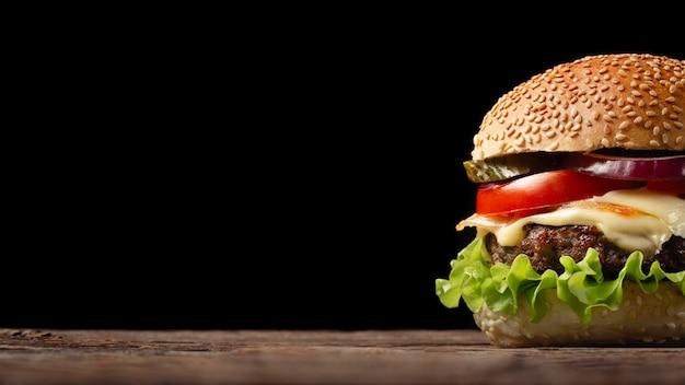 Primer plano de hamburguesa casera con carne de res, tomate, lechuga, queso y cebolla en mesa de madera.