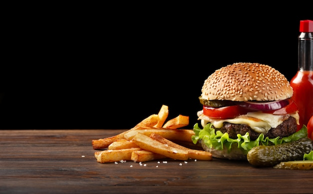 Primer plano de hamburguesa casera con carne, tomate, lechuga, queso, papas fritas salsa botella en mesa de madera.