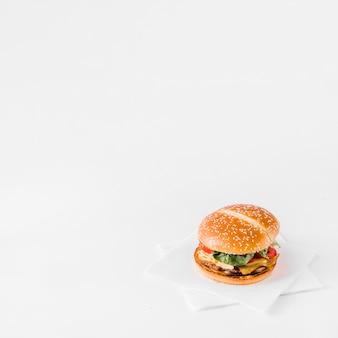 Primer plano de hamburguesa fresca sobre papel de seda sobre fondo blanco