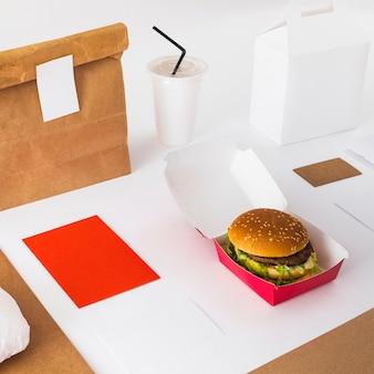 Primer plano de hamburguesa fresca con taza de eliminación y paquete de alimentos