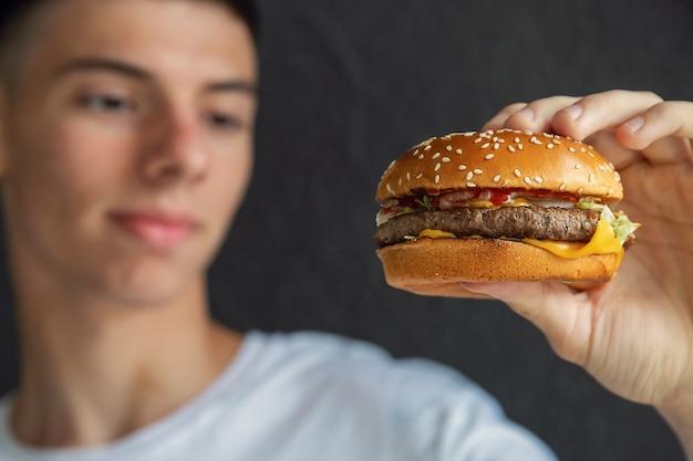 Primer plano, de, hamburguesa, en, manos, de, joven, mirarlo, con, apetito
