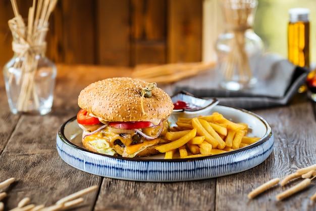 Primer plano de una hamburguesa con queso con papas fritas