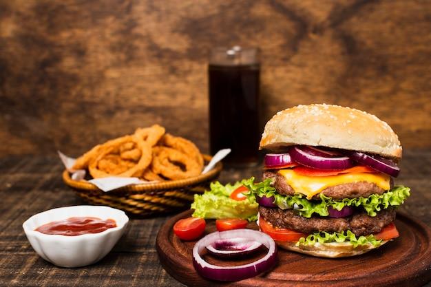 Primer plano de hamburguesa con soda y aros de cebolla