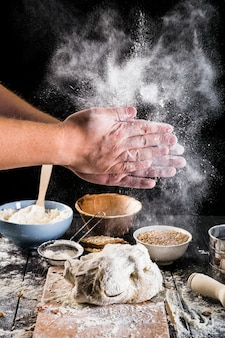 Primer plano de harina de polvo de la mano del panadero en la masa con los ingredientes en la mesa
