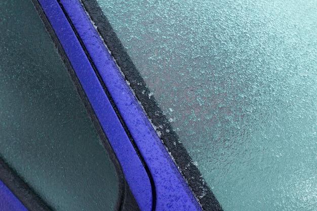 Primer plano de una helada en el coche azul durante el invierno