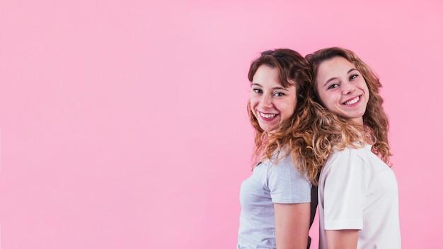 Primer plano de la hermana de pie espalda con espalda sobre fondo rosa