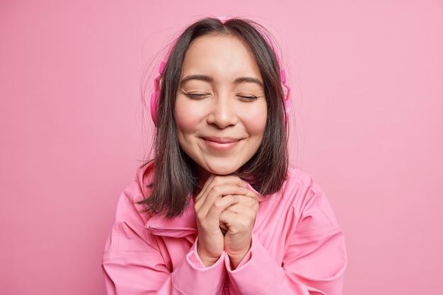 Primer plano de la hermosa adolescente asiática mantiene las manos debajo de la barbilla, cierra los ojos con placer escucha a través de auriculares inalámbricos disfruta de la melodía favorita aislada sobre la pared rosa. concepto de hobby