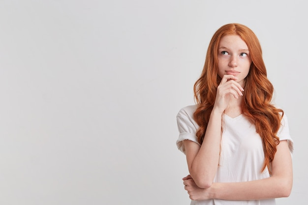 Primer plano de una hermosa joven pelirroja sonriente con pelo largo ondulado