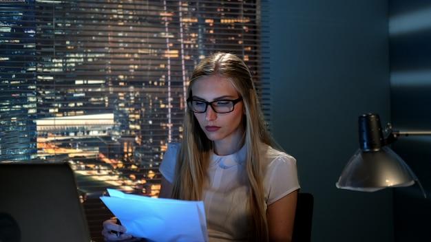 Primer plano de hermosa maestra en anteojos revisando el resumen de alguien en casa