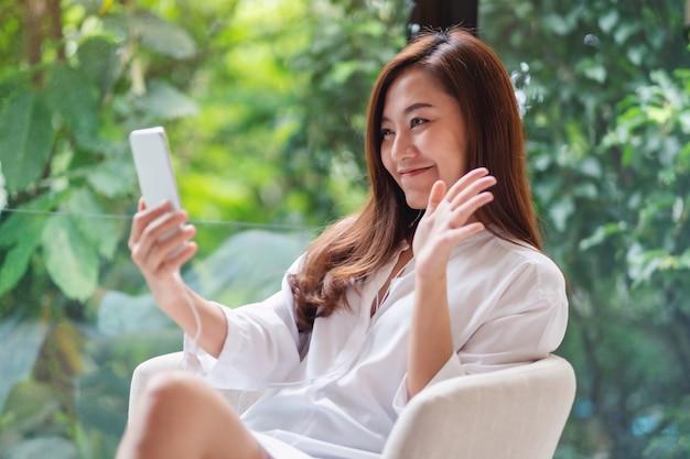 Primer plano de una hermosa mujer asiática agitando las manos mientras usa el teléfono móvil para una video llamada en casa