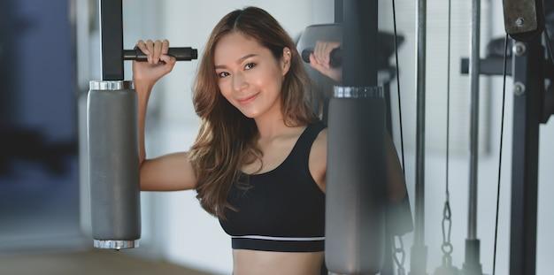 Primer plano de hermosa mujer asiática con ejercicio de cuerpo bronceado y delgado en la máquina