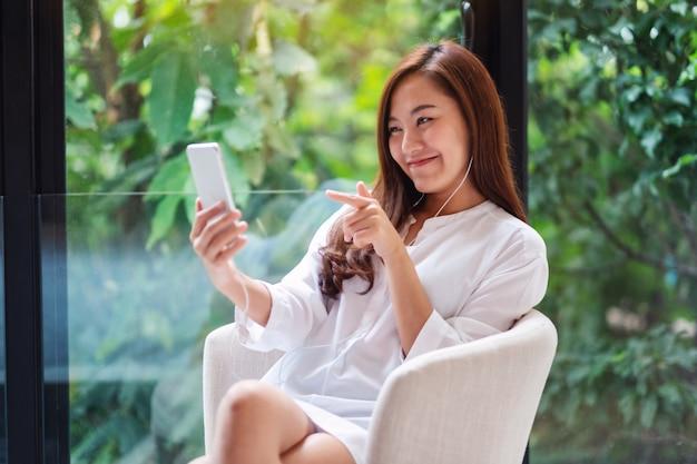 Primer plano de una hermosa mujer asiática que usa el teléfono móvil para videollamadas en casa