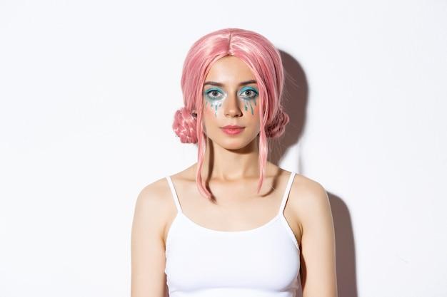 Primer plano de hermosa mujer celebrando halloween en traje de hada, con peluca rosa y maquillaje brillante, de pie.