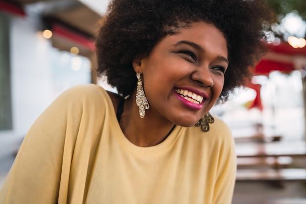 Primer plano de una hermosa mujer latina afroamericana sonriendo y pasando un rato agradable en la cafetería.
