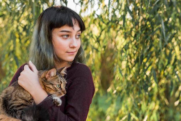 Primer plano de una hermosa mujer sonriente abrazando a su gato atigrado en el parque