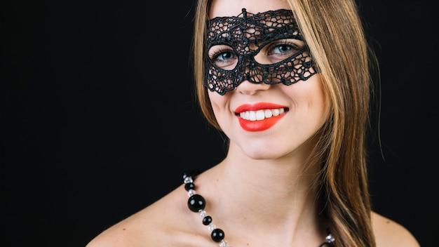 Primer plano de una hermosa mujer sonriente en máscara de carnaval negro