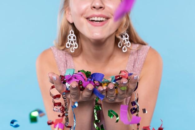 Primer plano hermosa mujer sosteniendo confeti